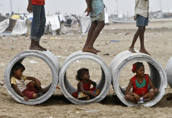 Children sitting inside cement water pipes play on the Marina beach Marina beach in Chennai